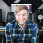 A picture of Kevin Winebarger smiling in front of a studio setup.